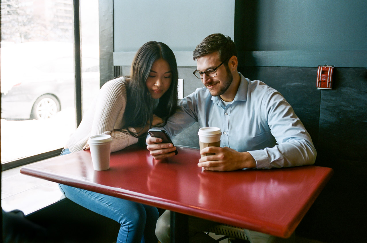 Man and woman in coffeeshop looking at mobile phone