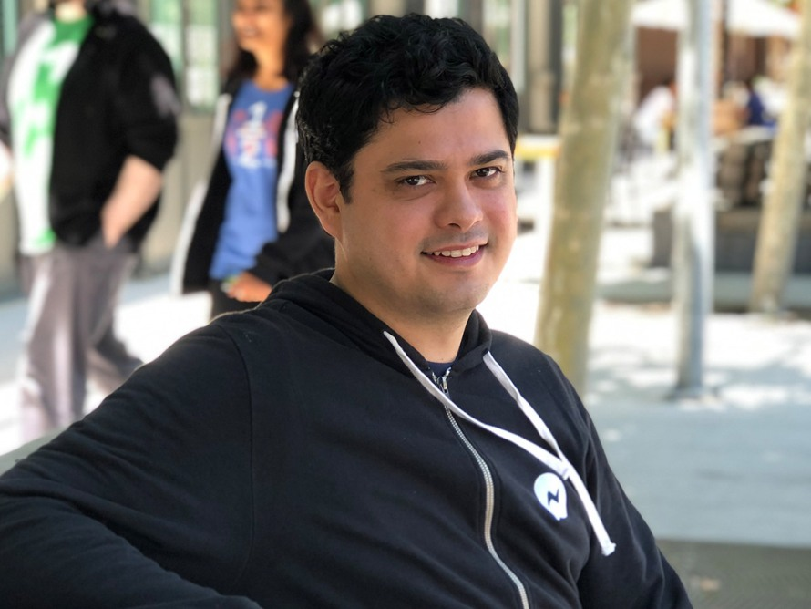 male employee Alberto B seated and smiling outdoors