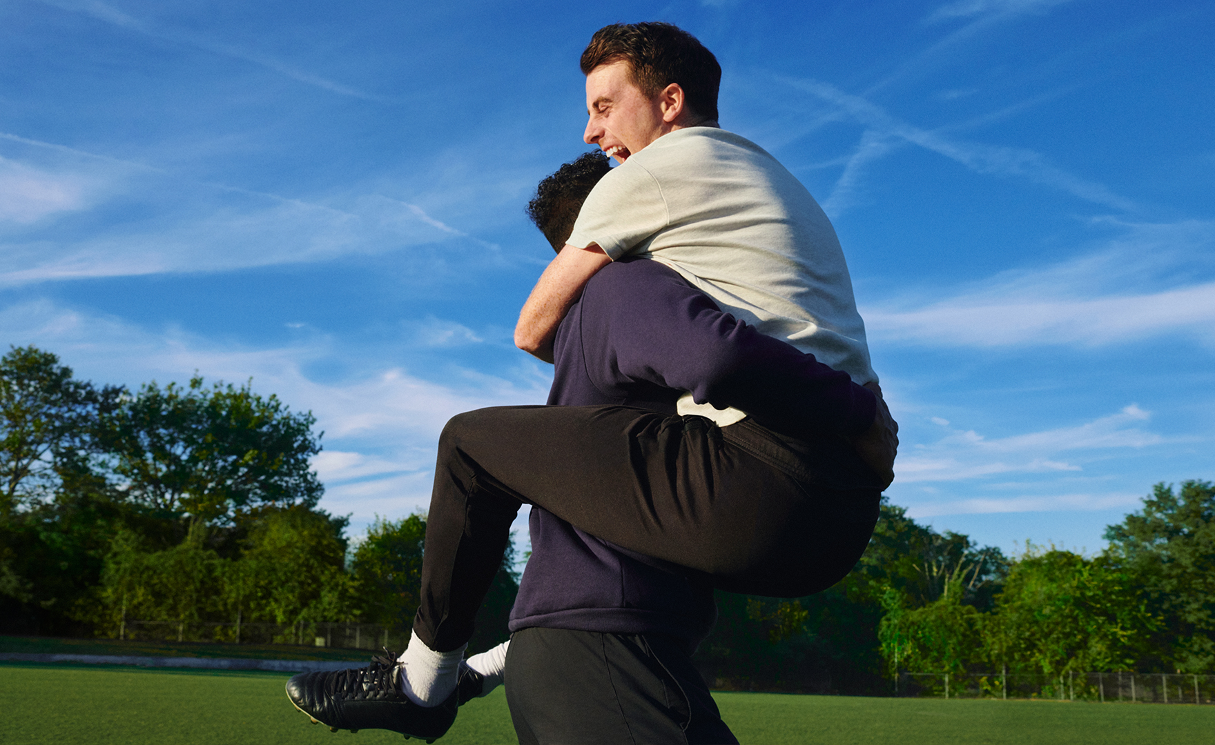 two young adult male adult soccer players outdoors embracing with elation