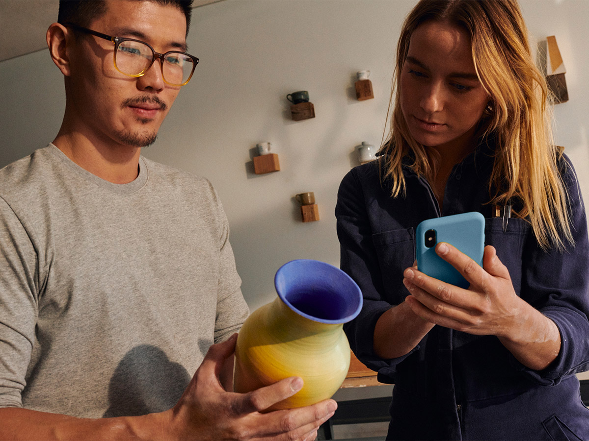 young man holding pottery and young woman with mobile phone engaged in payment transaction