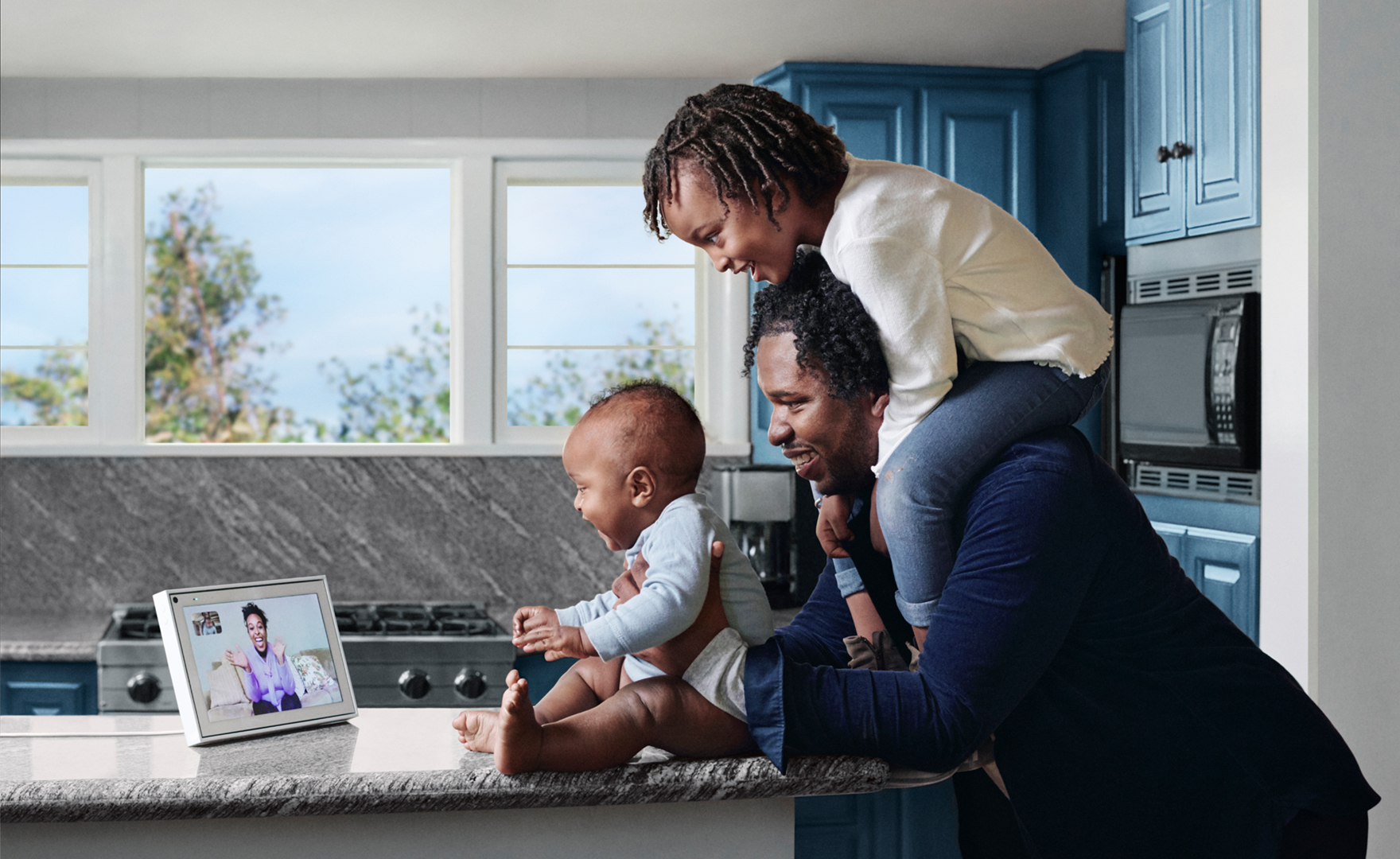 father with two children in kitchen conversing with grandmother via Portal device