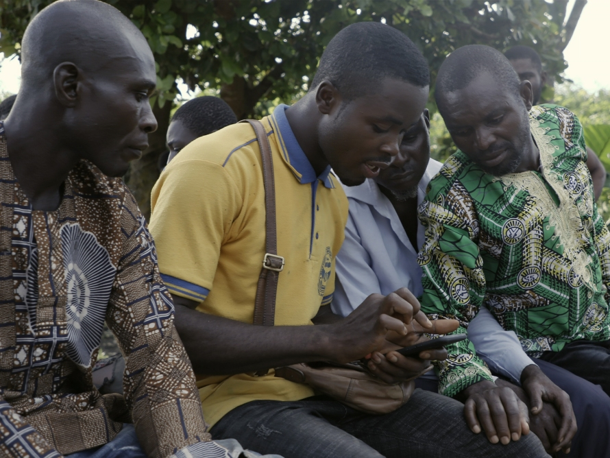 Four men looking at a mobile phone