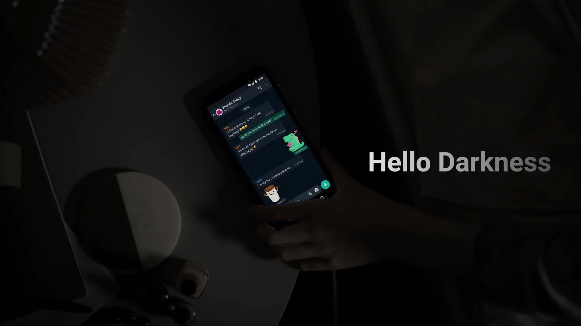 Screenshot of WhatsApp dark mode video (a hand reaching for a phone in a dark room)