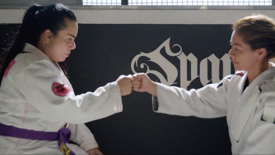 Photo of women on Jiu Jitsu mat giving each other a fist bump