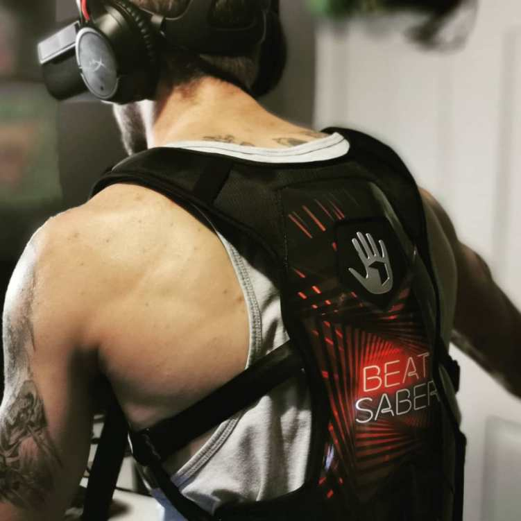 Photo of a gamer wearing Beat Saber SUBPAC and VR headset