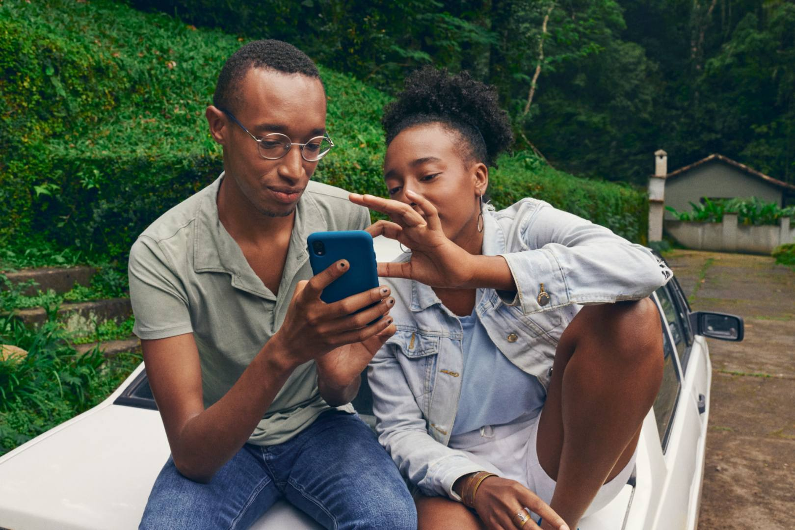 Image of two people resting on a car while looking at a phone screen together.