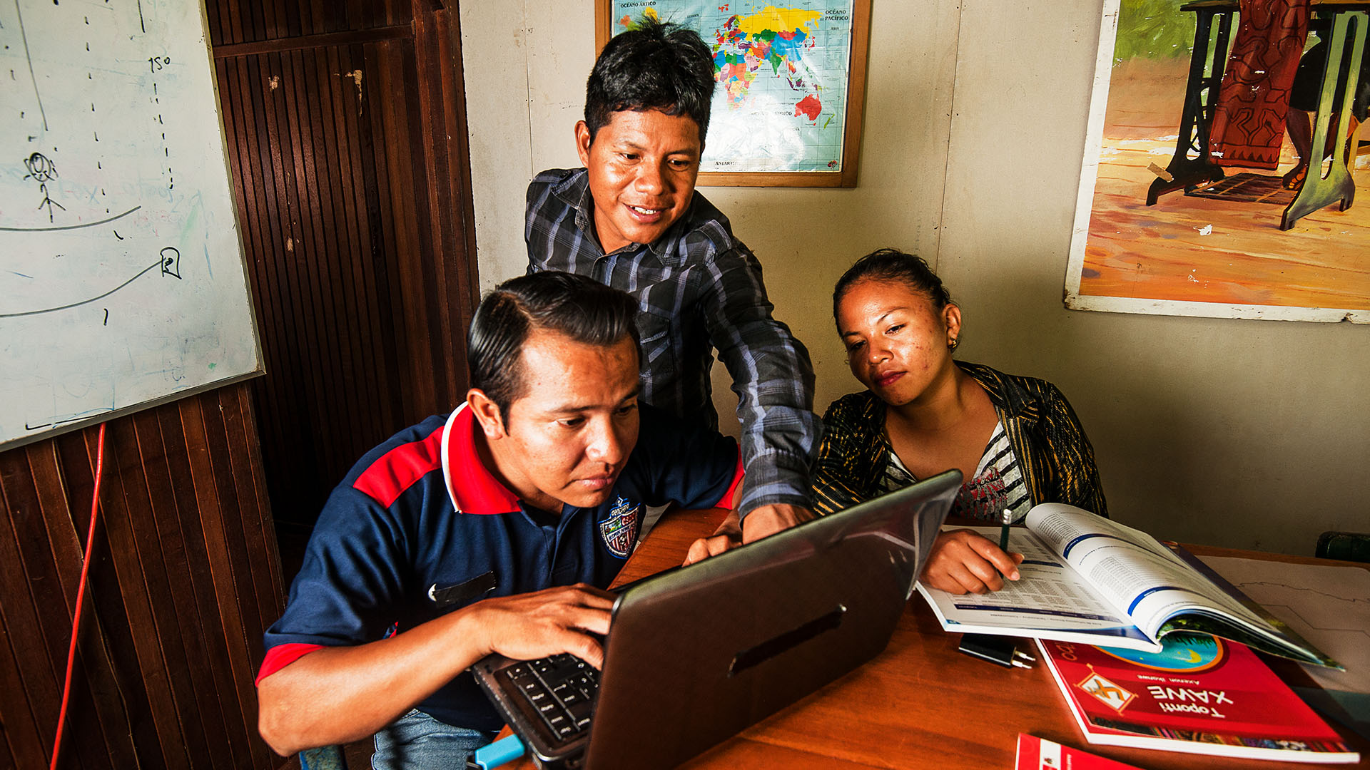 Three people working together at a computer