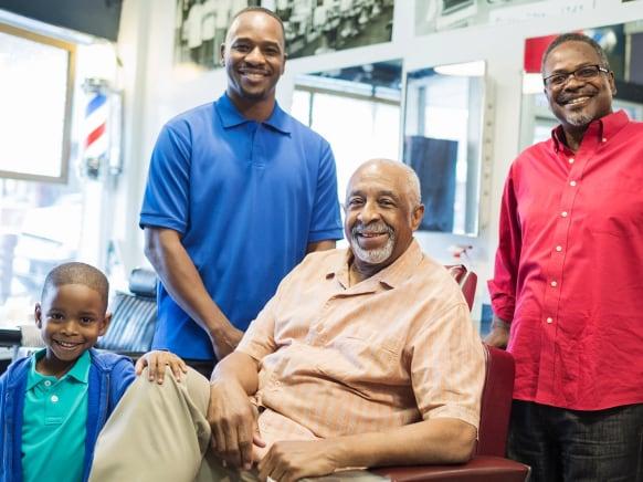 4 generations of men inside a barbershop smiling at the camera