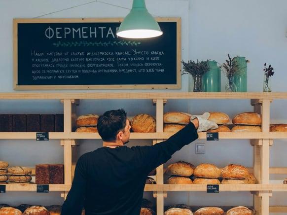 Man inside bakery reaching for bread on a shelf