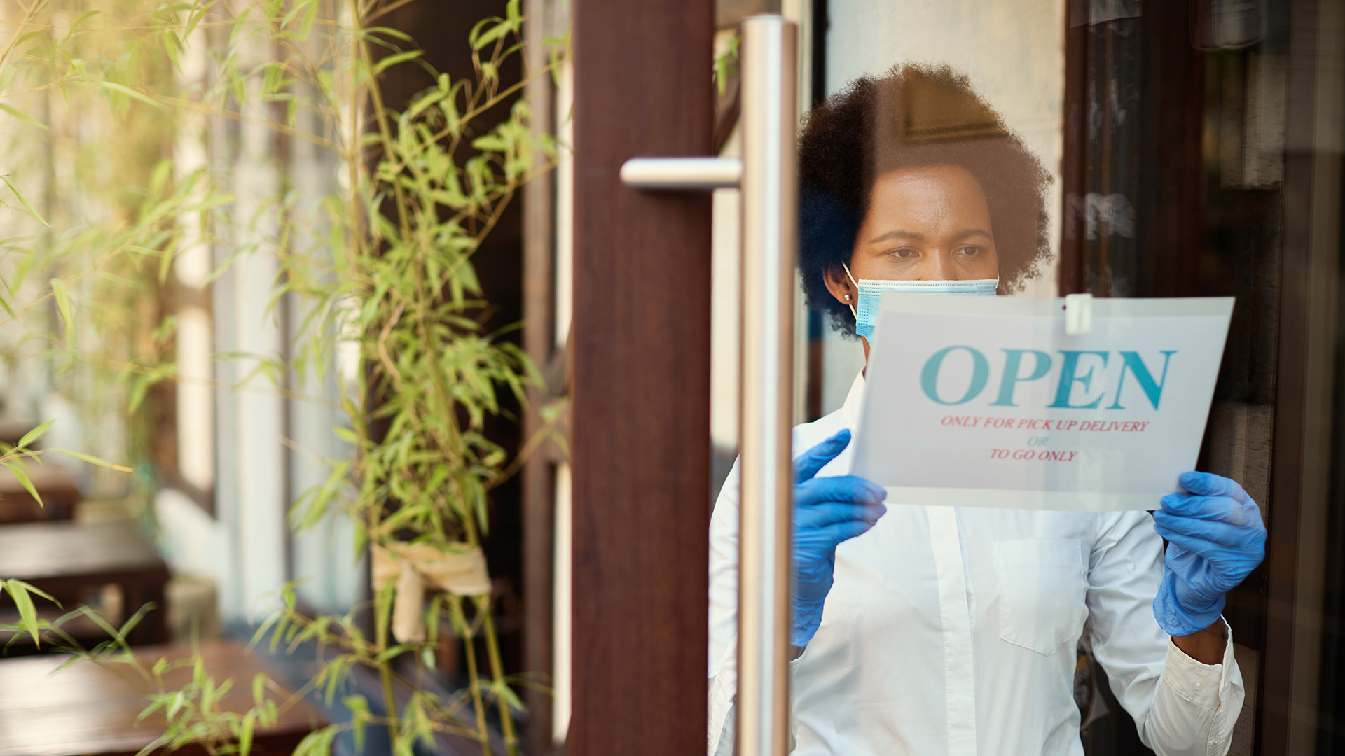 "Photo of a woman placing an ""Open"" sign on the door of a business"