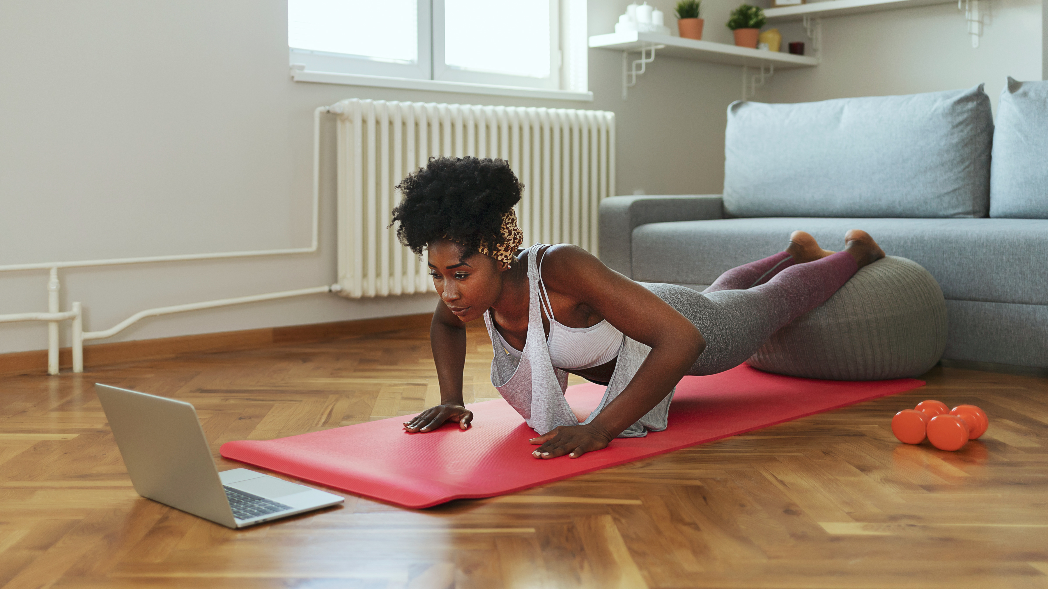 woman doing yoga in front of computer