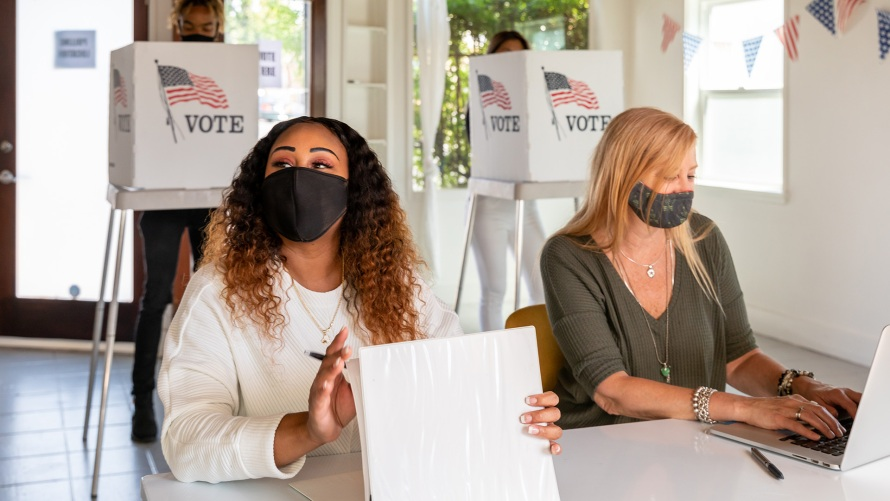 two women working at the polls
