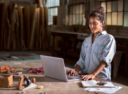 woman using a laptop in a woodshop