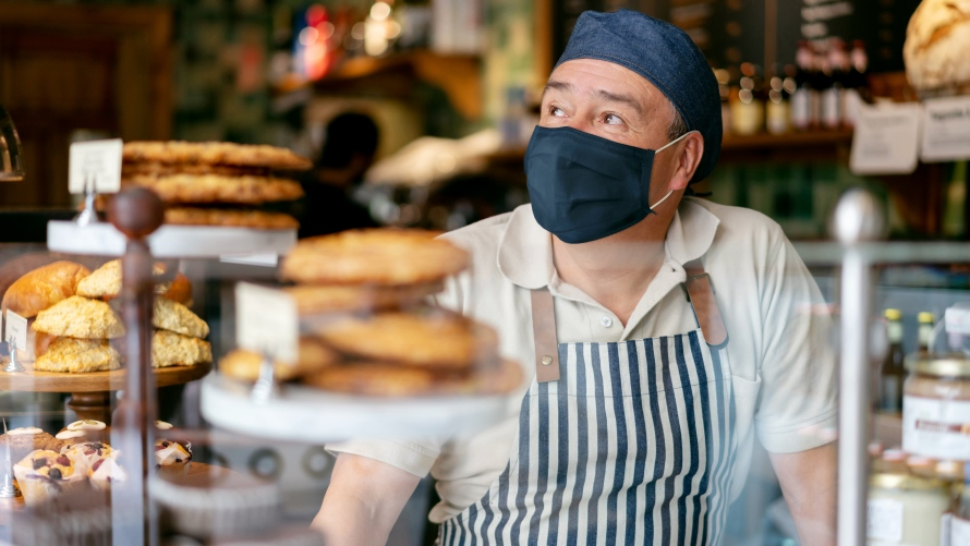 Man in mask working behind bakery counter