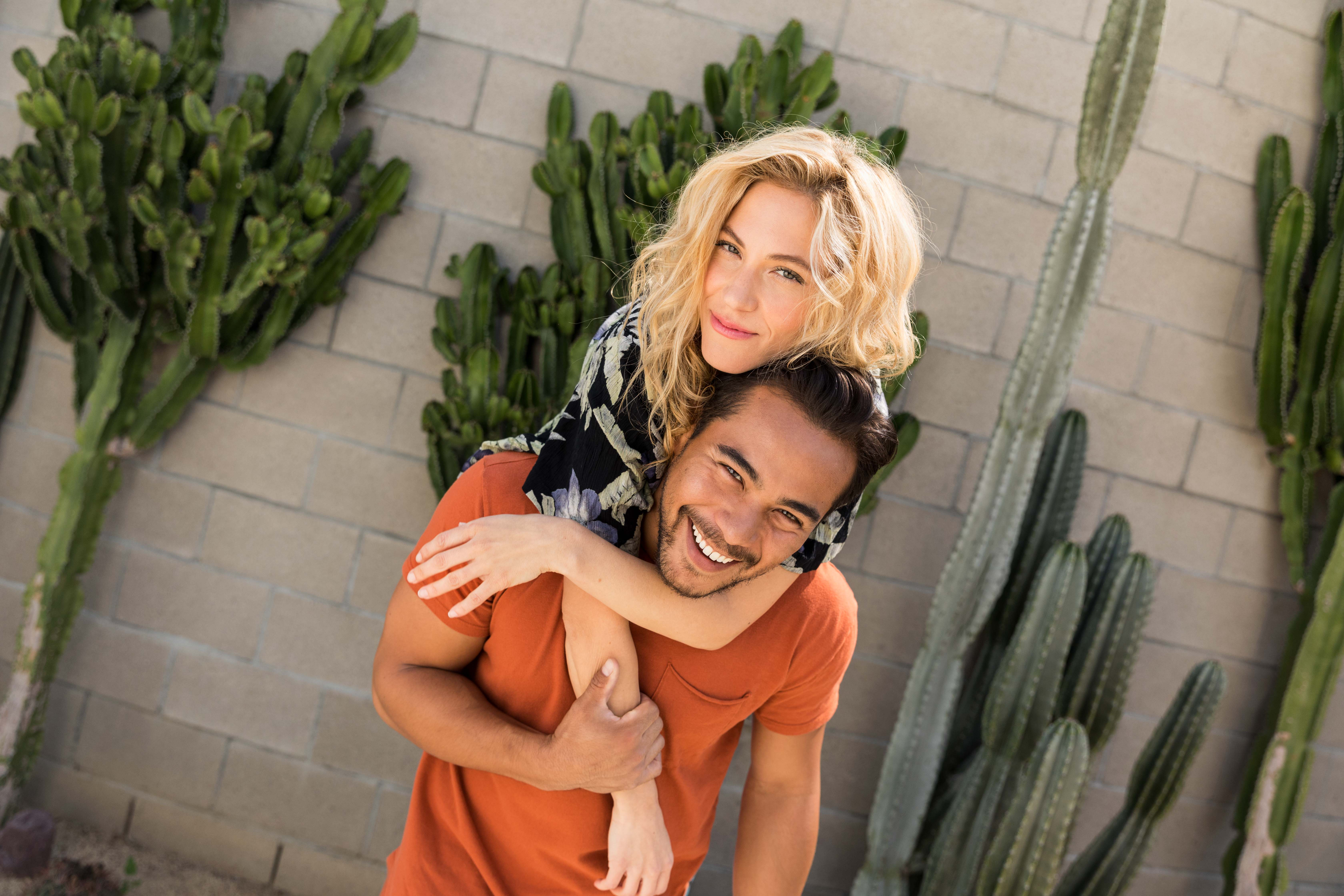 A couple posing in front of cactus.