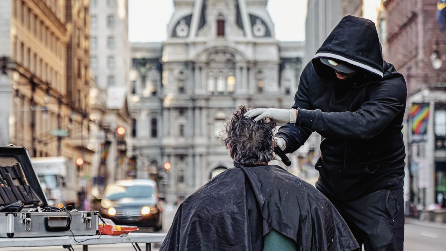 Photo of a man giving another man a haircut in the street.