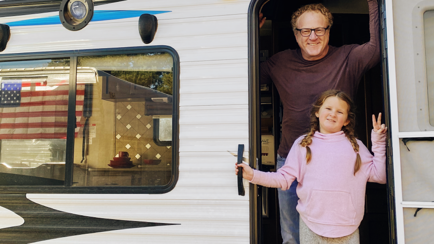 Photo of Woody Faircloth and his daughter posing in the doorway of an RV.