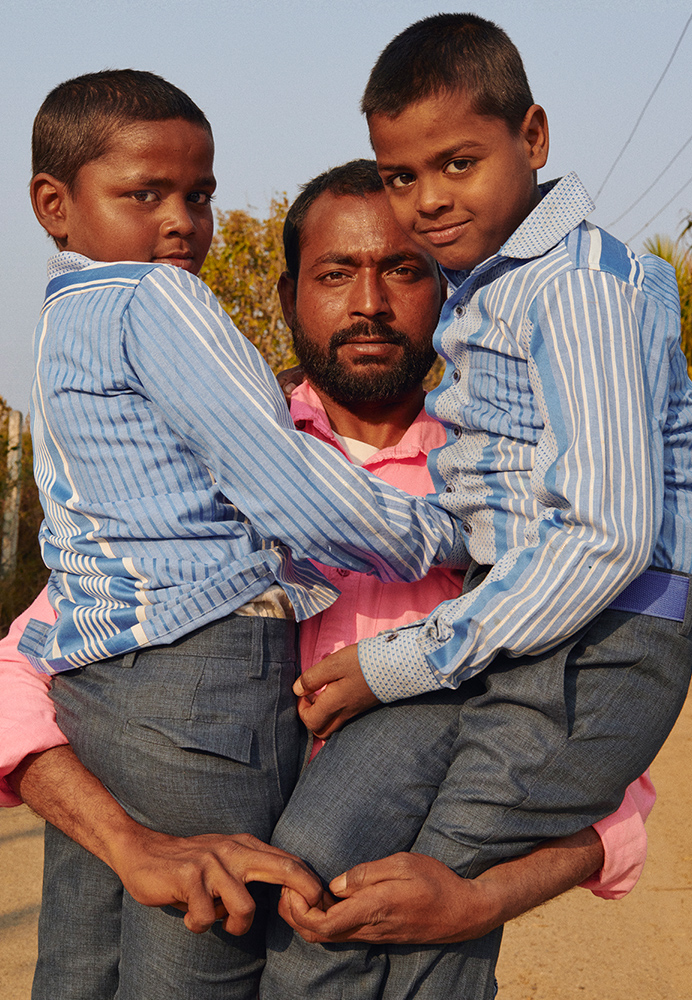 Photo of man carrying two boys