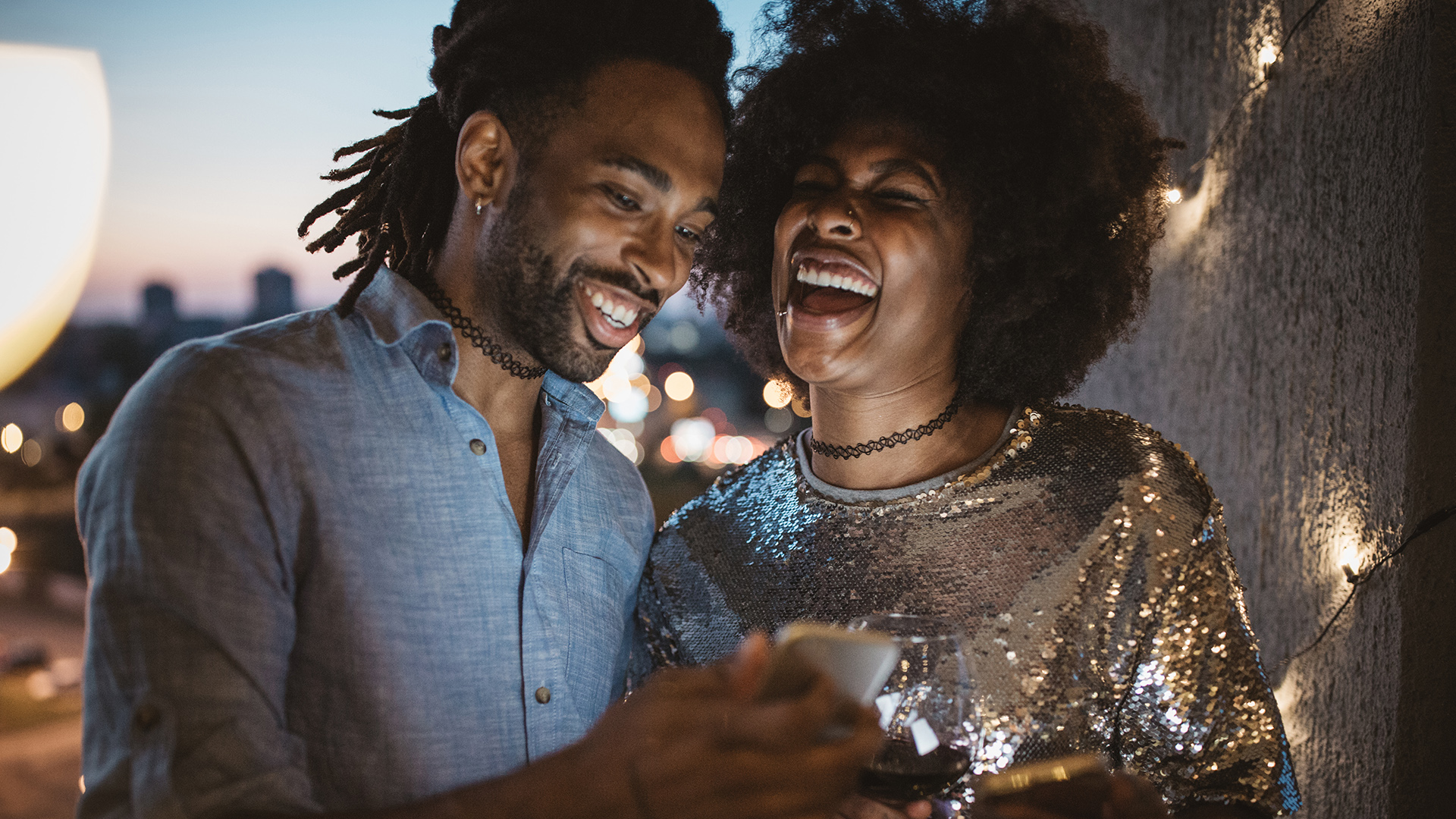Man and woman laughing outside, looking at phone
