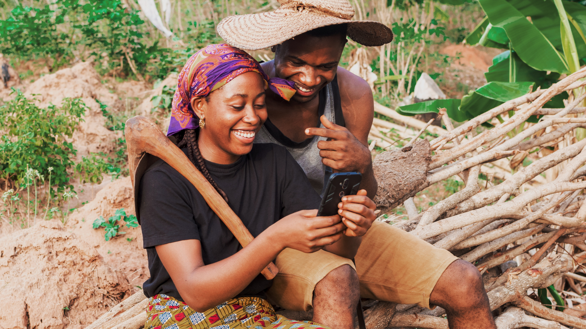 Photo of two people in a rural area looking at a phone