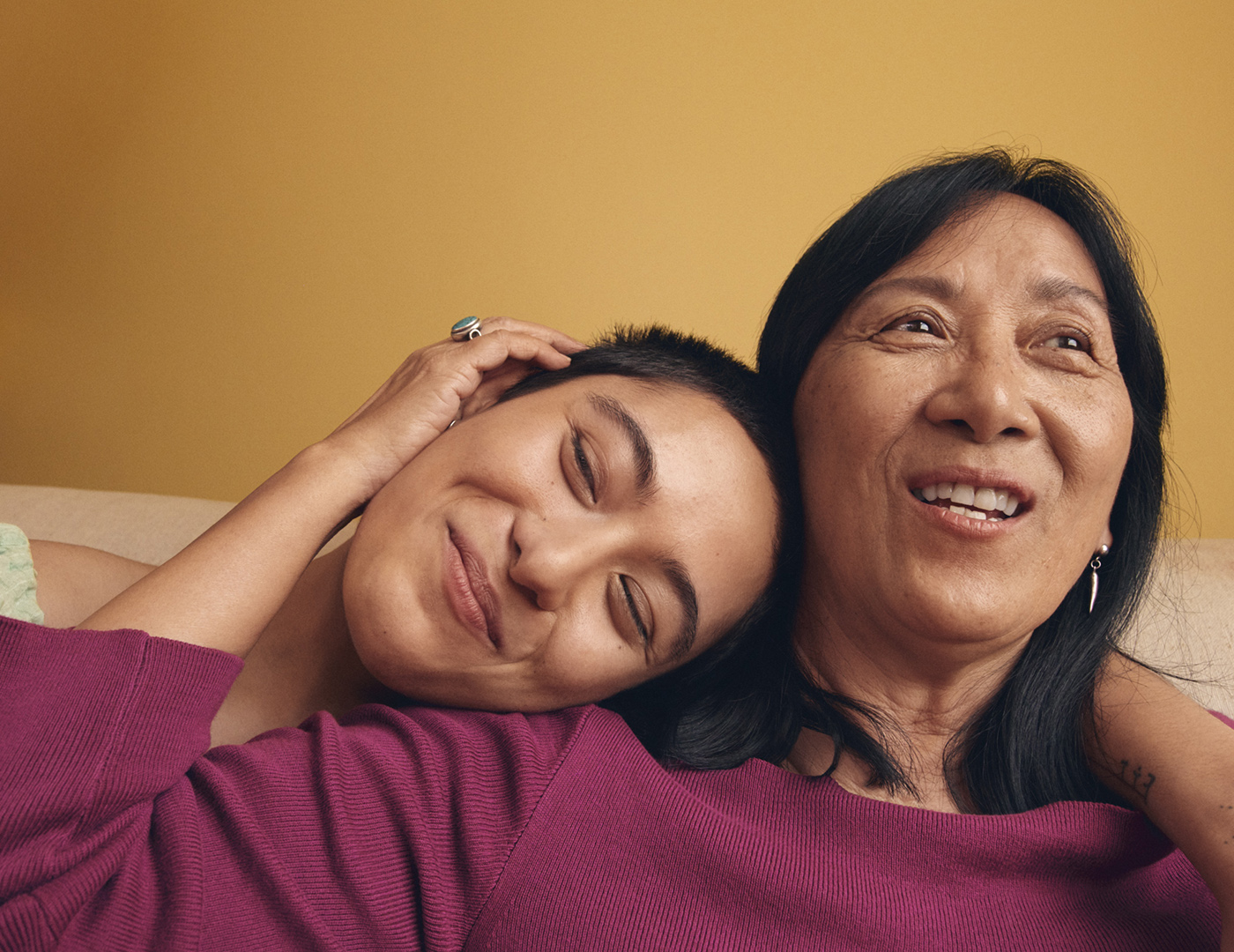 Photo of a woman leaning her head on another woman's shoulder, both smiling