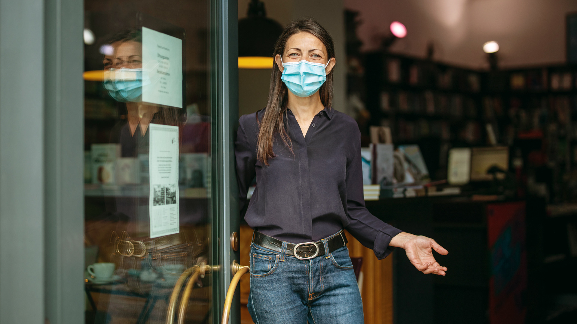 Picture of a woman in front of store wearing a mask